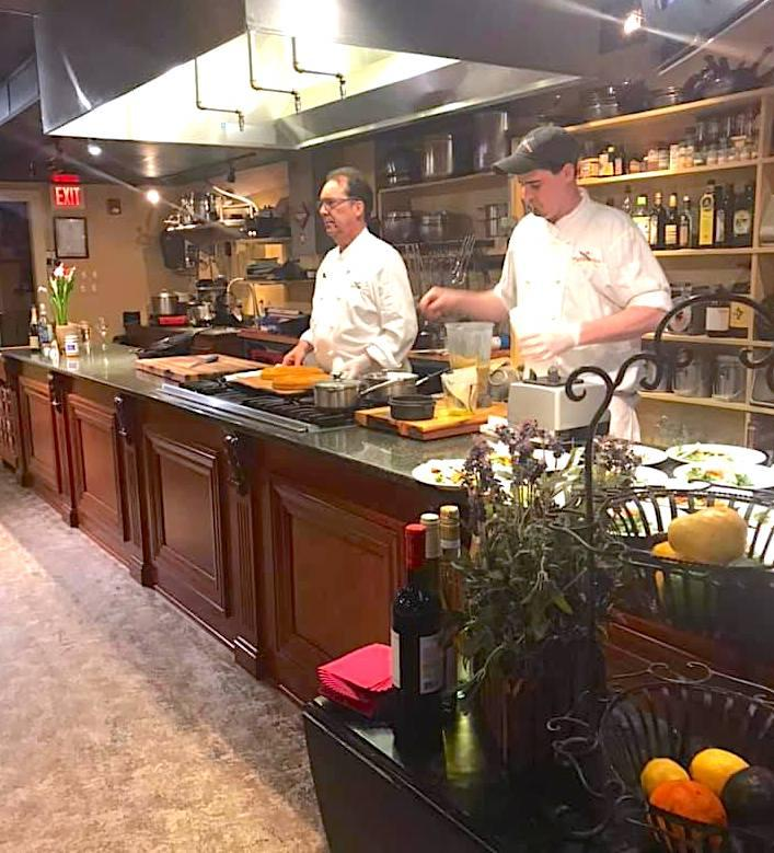 Head chef and assistant chef entertaining guests with cooking demonstrations on a stage kitchen