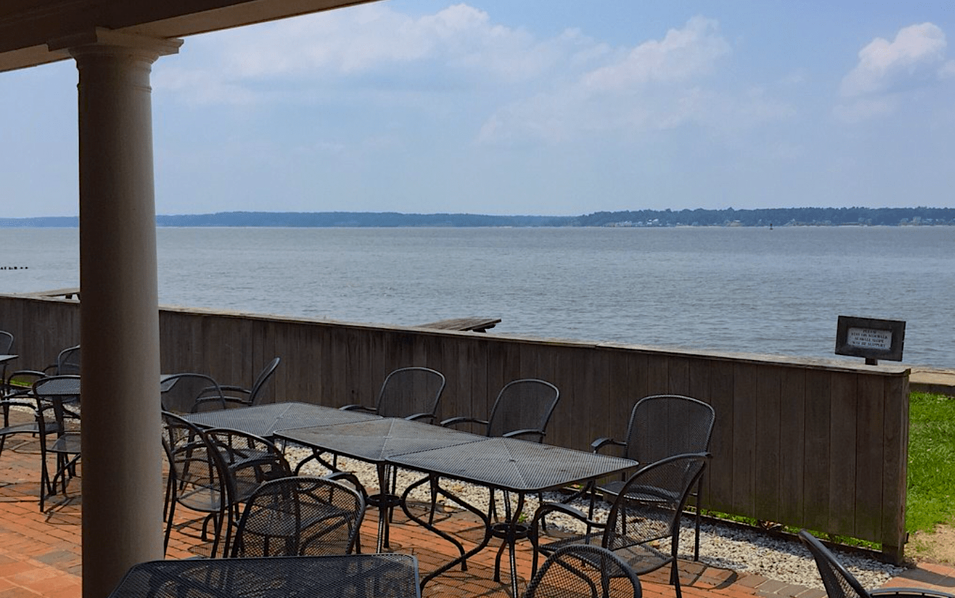 Outdoor seating at Dale House Cafe at Historic Jamestowne overlooking the waterfront of the river.